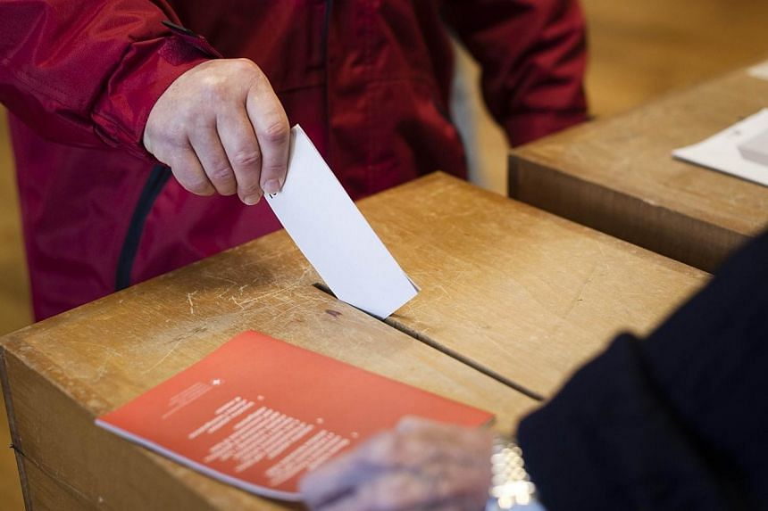 A man casts his ballot during a nationwide popular vote at a polling station in Ascona on Sunday, Feb 9, 2014. Swiss voters were split down the middle on Sunday on whether to curb immigration by European Union citizens, a polling agency sai