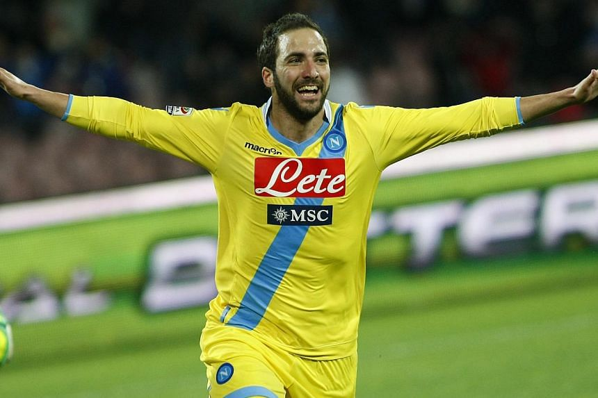 Argentine forward Gonzalo Higuain celebrates after scoring a goal during the Italian Serie A football match between SSC Napoli and AC Milan in San Paolo Stadium on Feb 8, 2014. Higuain scored his 11th and 12th goals of the season as Napoli outclassed