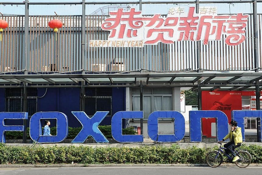 This picture taken on Feb 22, 2013, shows people walking past a Foxconn recruitment point in Shenzhen, south China's Guangdong province. Foxconn group has signed a letter of intent to invest up to US$1 billion (S$1.27 billion) in Indonesia as it seek