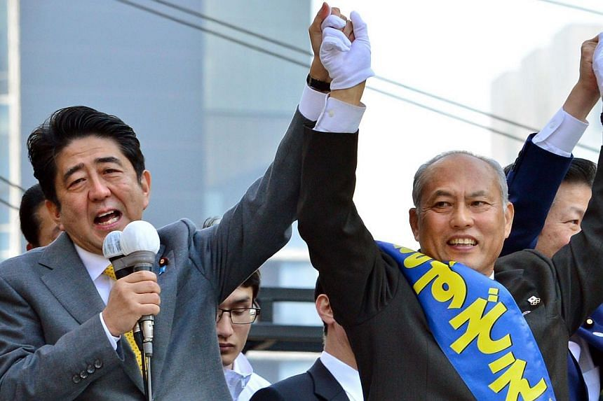 This file picture taken on February 2, 2014 shows Japanese Prime Minister and ruling Liberal Democratic Party (LDP) President Shinzo Abe (left) delivering a speech to support former health minister Yoichi Masuzoe (right) during Mr Masuzoe's election