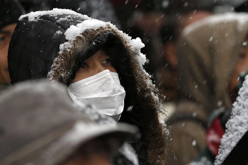 Voters listen to an election campaign speech by former Japanese Prime Minister and candidate in the Tokyo gubernatorial election Morihiro Hosokawa on Feb 8, 2014. Tokyo residents braved through the snow on Sunday to go to the polls to choose a new go