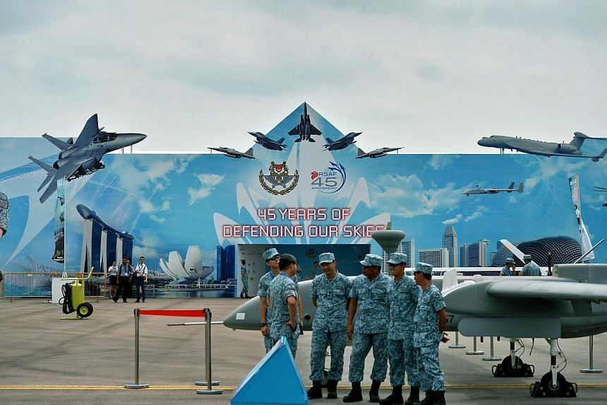 Airforce personnel near the Republic of Singapore Airforce exhibition room at the Singapore Airshow 2014 held at the Changi Exhibition Centre. More than 80 military and commercial aircraft from some 47 countries will be on display at this year's Sing