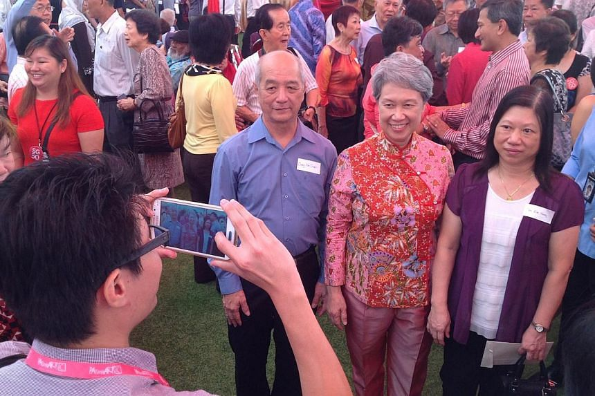Madam Ho Ching (in red) with guests of the pioneer generation at the Istana.-- ST PHOTO: GOH CHIN LIAN