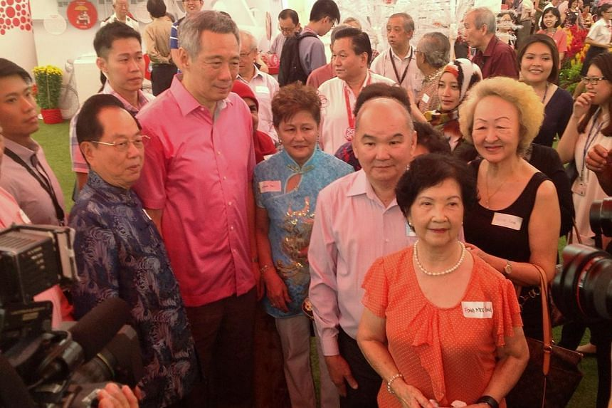 PM Lee (left, in red) with guests of the pioneer generation at the Istana.-- ST PHOTO: GOH CHIN LIAN