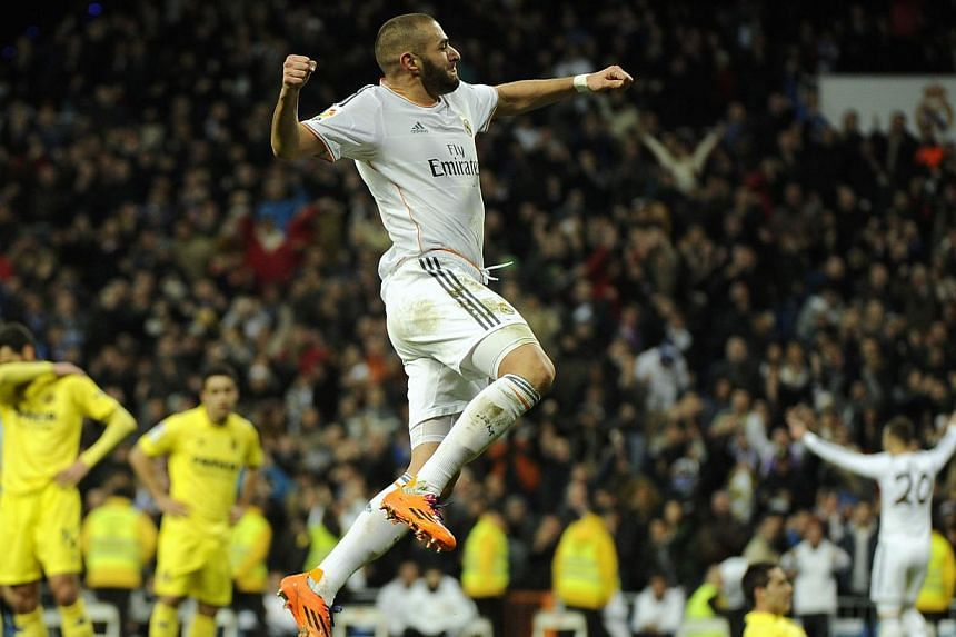 Real Madrid's French forward Karim Benzema celebrates after scoring during their Spanish league football match against Villarreal at the Santiago Bernabeu stadium in Madrid on Feb 8, 2014. Gareth Bale compensated for the absence of the suspended