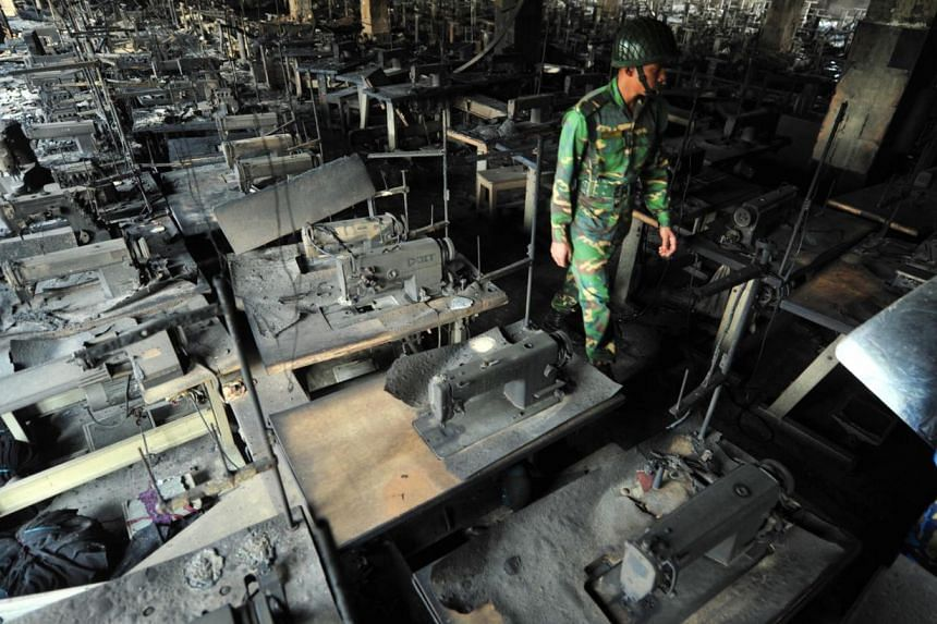 In this photograph taken on Nov 25, 2012, a Bangladeshi Army personel walks through rows of burnt sewing machines after a fire in the nine-storey Tazreen Fashion plant in Savar, about 30 kilometres north of Dhaka. Owners of a Bangladesh garment facto