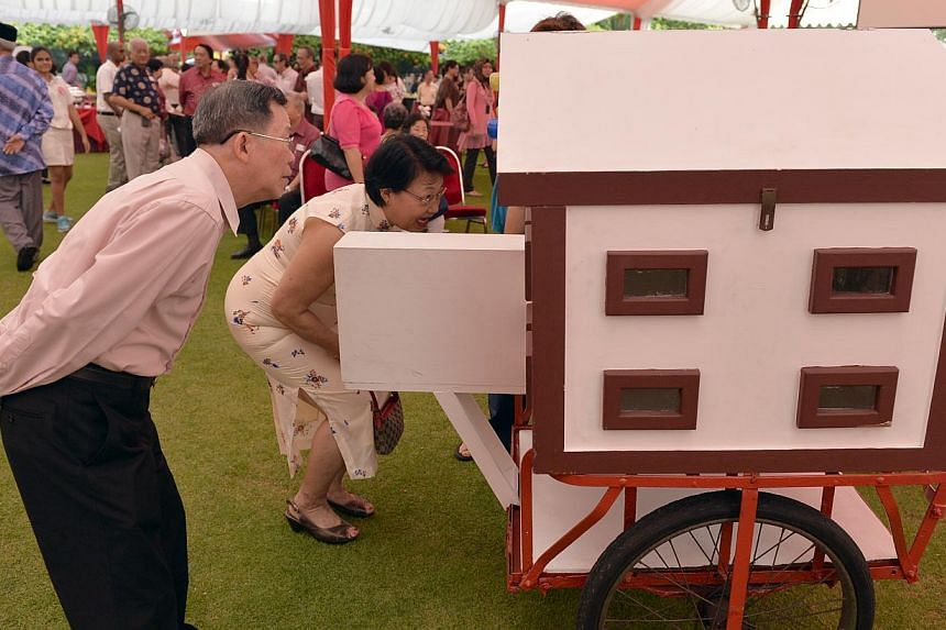 Mr Ho Khoon Thye and Mrs Lim Yock Eng peering into a replica peep-show cart from the 60's and 70's. -- ST PHOTO: DESMOND FOO