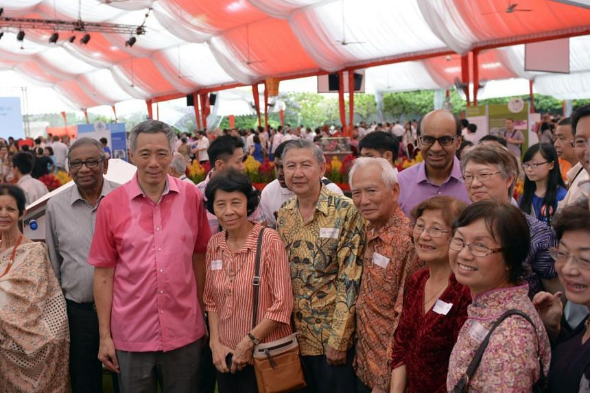 Prime Minister Lee Hsien Loong (third from left) and Deputy Prime Minister Tharman Shanmugaratnam with invited guests at the Pioneer Generation tribute event at the Istana, on Sunday, Feb 9, 2014. The cut-off age of 65 for those who stand to benefit