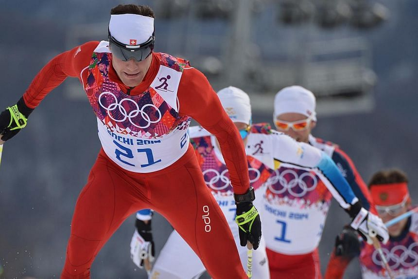 Switzerland's Dario Cologna is chased by Sweden's Marcus Hellner (11) and Norway's Martin Johnsrud Sundby (1) as they compete in the Men's Cross-Country Skiing 15km + 15km Skiathlon at the Laura Cross-Country Ski and Biathlon Center during the Sochi