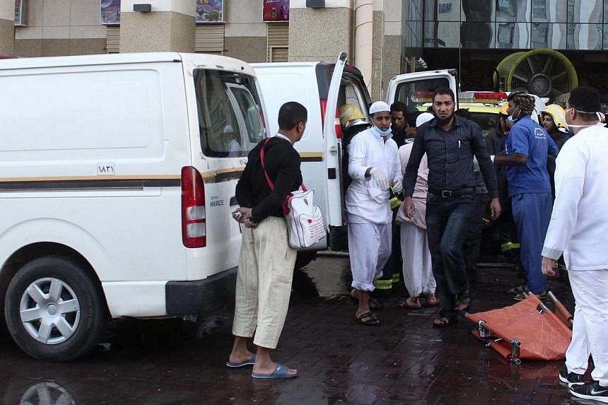 Emergency personnel wait to evacuate injured people after a fire broke out in a hotel, in Medina on Feb 8, 2014. Fifteen people died and around 130 were injured when a fire broke out in a hotel packed with Muslim pilgrims in the Saudi Arabian city of