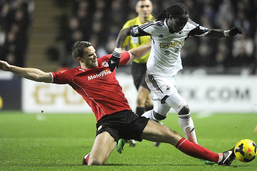 Swansea City's Marvin Emnes (right) is challenged by Cardiff City's Ben Turner during their English Premier League soccer match at the Liberty Stadium in Swansea, Wales, on Feb 8, 2014. -- PHOTO: REUTERS
