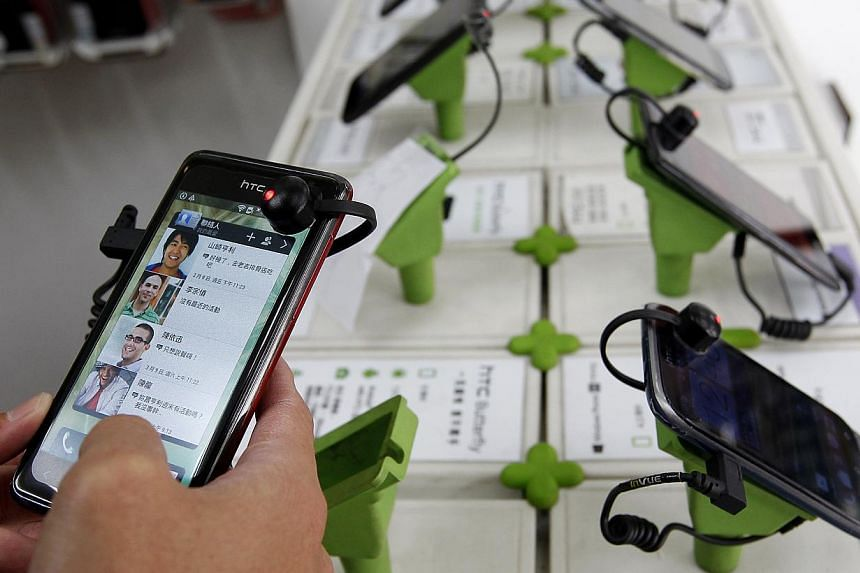 A customer plays with an HTC J smartphone in a mobile phone shop in Taipei in this April 8, 2013, file photo. Smarting from growing losses, Taiwanese phone maker HTC Corp says it will expand its range of cheaper products as it fixes off-target market