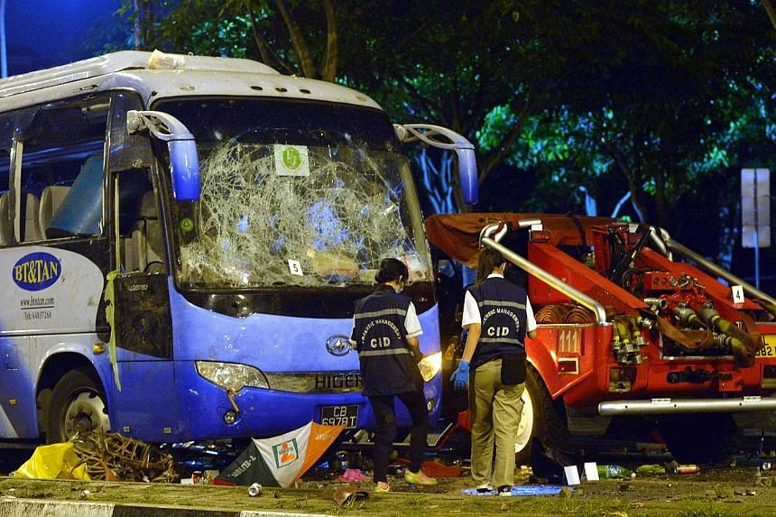 Police officers examining the wrecked private bus at the aftermath of the Little India riot in the early hours on Dec 9, 2013. A 32-year-old Indian national was sentenced to 15 weeks in jail on Monday for his role in last December's Little India