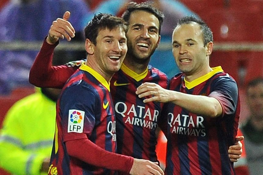 Barcelona's midfielder Cesc Fabregas (centre) celebrates with Argentinian forward Lionel Messi (left) and midfielder Andres Iniesta after scoring during the Spanish league football match Sevilla vs FC Barcelona at the Ramon Sanchez Pizjuan stadium in