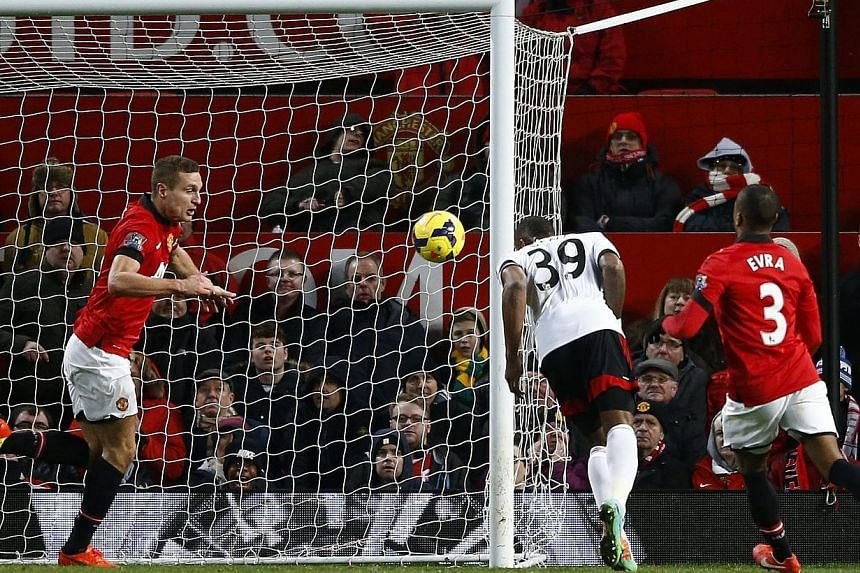 Fulham's Darren Bent (centre) heads and scores against Manchester United during their English Premier League soccer match at Old Trafford in Manchester, northern England, Feb 9, 2014. An injury-time goal from Bent inflicted more pain on champions Man