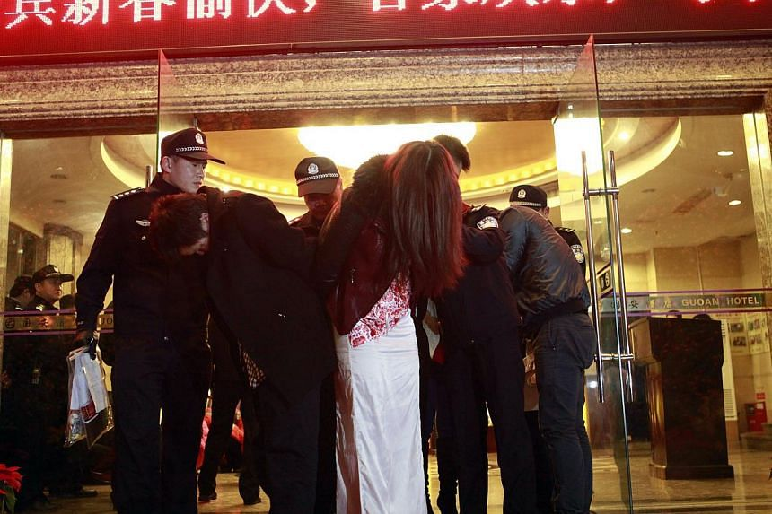 """Chinese police taking away alleged sex workers and clients at an entertainment center in Dongguan, southern China's Guangdong province, on Feb 9, 2014. Chinese authorities have carried out a rare crackdown on the sex trade in the """"sin city"""" of Donggu"""