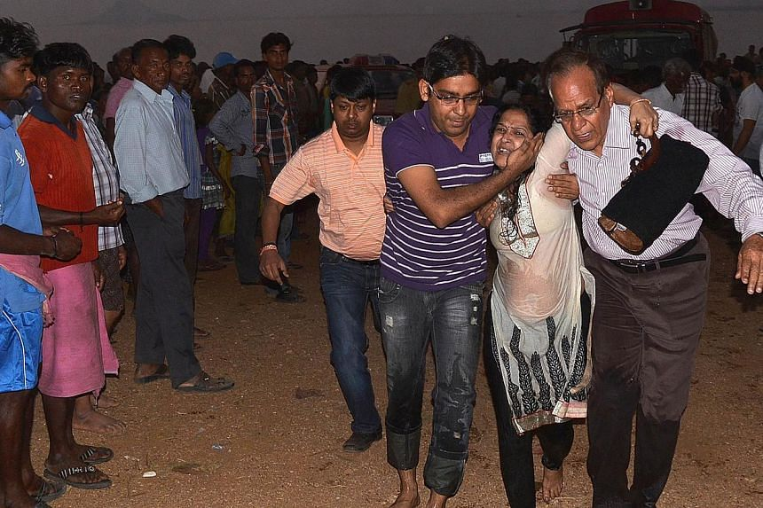 A survivor of a boat capsize is assisted atHirakud reservoir in Sambalpur district, some 320km from Bhubaneswar, on Feb 9, 2014. An overloaded passenger boat has capsized in a river in eastern India, leaving 29 people confirmed dead as rescuers