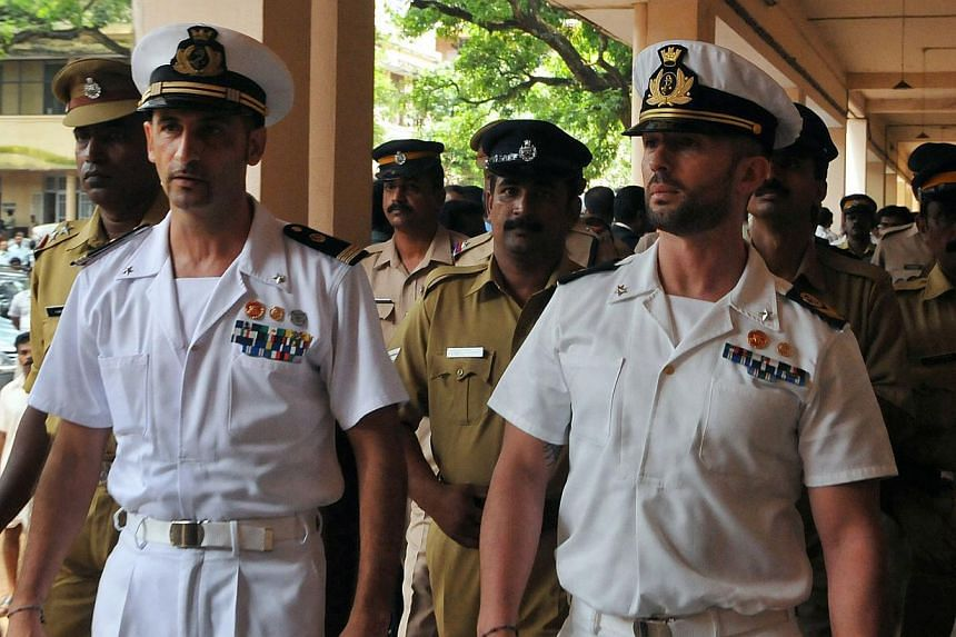 Italian marines Latore Massimiliano (second from left) and Salvatore Girone (second from right) are escorted by Indian police outside a court in Kollam, on May 25, 2012. Italy said on Monday, Feb 10, 2014, that India's relations with Rome and with th