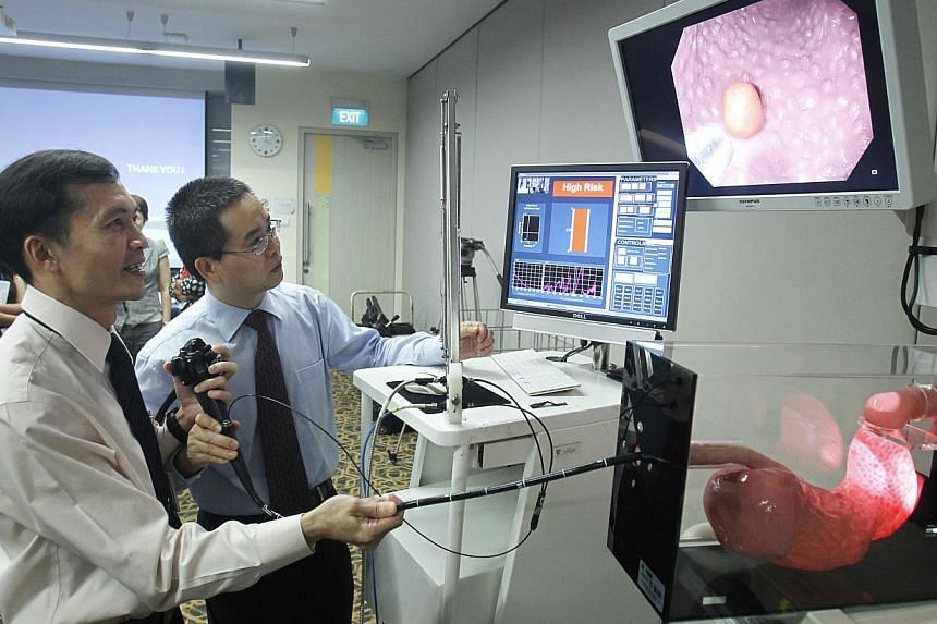 Professor Ho Khek Yu (left), head of Department of Medicine in NUS Yong Loo Lin School of Medicine, and Associate Professor Huang Zhiwei, from the Department of Biomedical Engineering in NUS Faculty of Engineering, demonstrate the detection of a mali