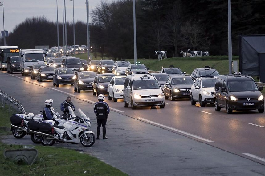 Police officers stand on the side of the road as taxi drivers demonstrate in their taxis, on Feb 10, 2014, near the Roissy Charles de Gaulle airport, outside Paris, to protest against competition from tourist transport vehicles. Taxi services out of