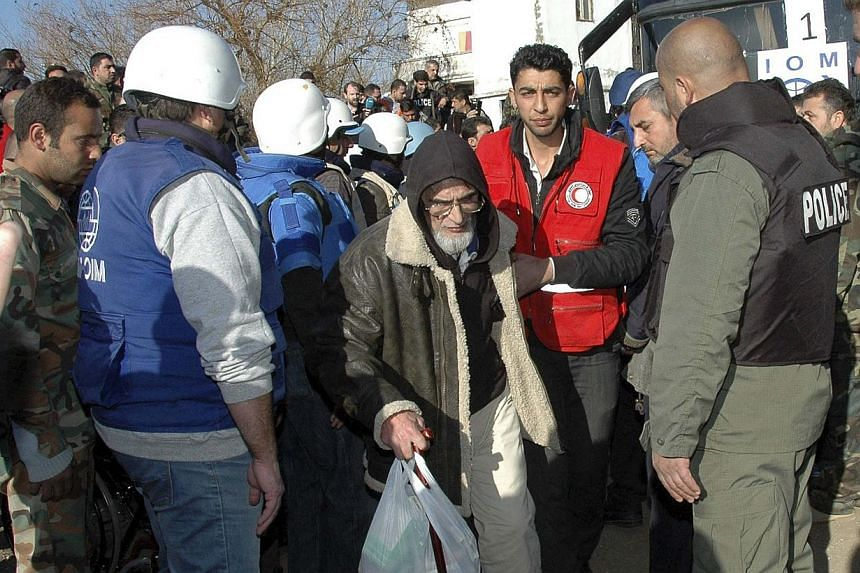 A Member of the Syrian Arab Red Crescent helps a man from a besieged area of Homs upon his arrival to the area under government control, on Feb 9, 2014. Aid teams prepared on Monday, Feb 10, 2014, to resume the evacuation of civilians from besieged n
