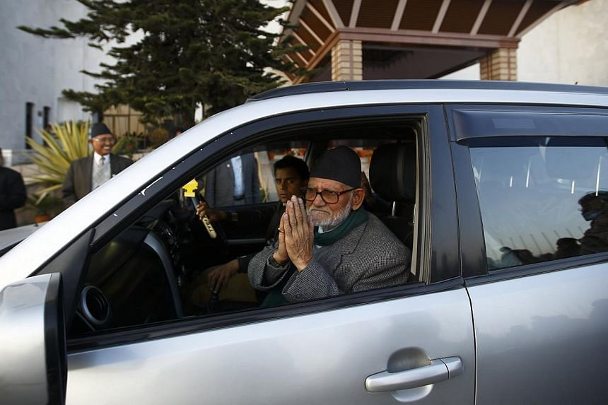 Mr Sushil Koirala, Chairman and parliamentary party leader for the Nepali Congress Party, greeting supporters from his vehicle as he leaves after filing his nomination for the post of prime minister in Kathmandu on Feb 9, 2014. -- PHOTO: REUTERS
