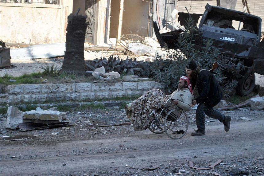 A civilian in a wheel chair is aided by an armed man ahead of being evacuated by United Nations (UN) staff, from the besieged district of the central Syrian city of Homs to a safer location, on Feb 9, 2014.Syria's warring sides headed on Monday