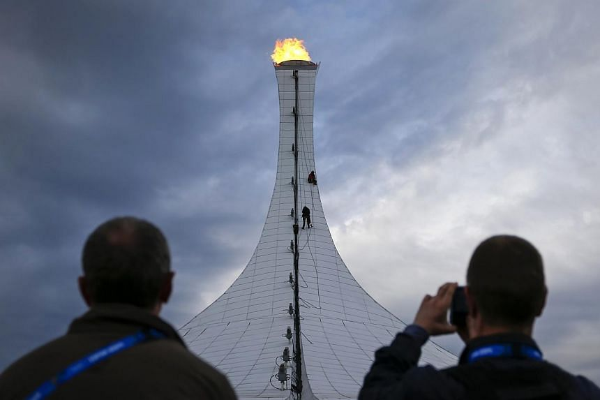 People watch as workers conducting maintenance rappel down on ropes from the top of the the Olympic Cauldron during the Sochi 2014 Winter Olympics on Feb 10, 2014.Western criticism of Russia's Winter Olympics was reminiscent of Cold War ambitio