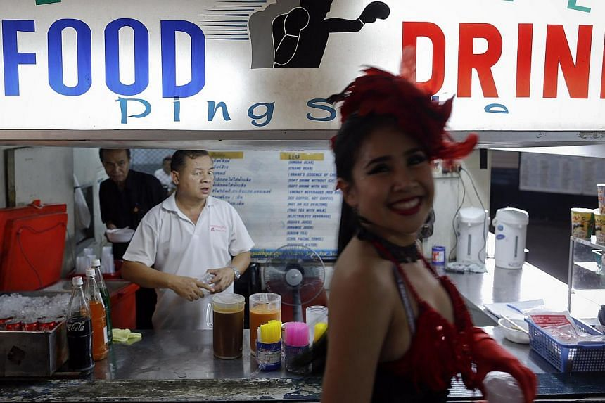 An entertainer passes by a ringside bar of Lumpinee stadium on Feb 7, 2014. -- FILE PHOTO: REUTERS