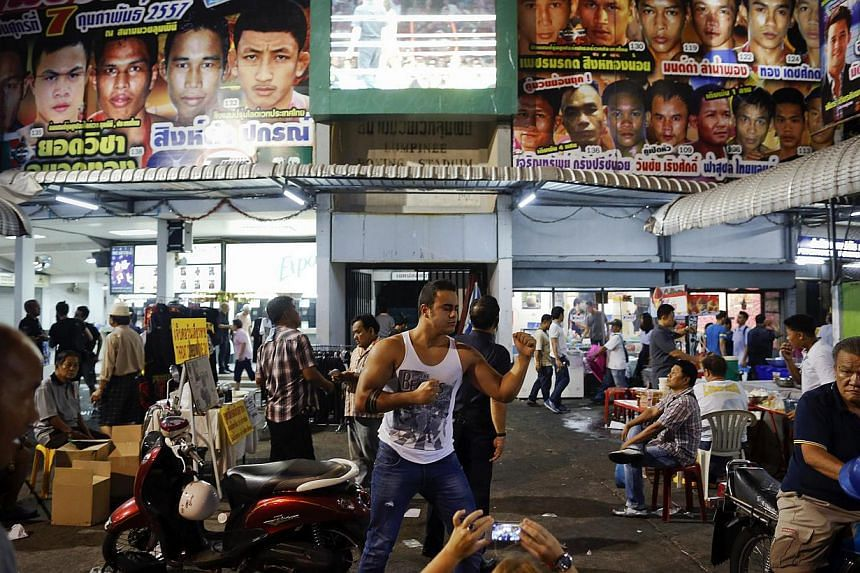 A tourist outside Lumpinee stadium on Feb 7, 2014, the venue's final fight night. The stadium will move to a new location on the outer fringes of the sprawling city - a logistical hassle for tourists and Thais who have flocked to Lumpinee for d
