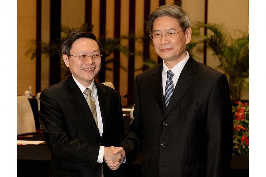 Taiwanese official Wang Yu-chi (L) who is in charge of the islands China policy shakes hands with his Chinese counterpart Zhang Zhijun from the Taiwan Affairs office (R) at the start of their meeting in Nanjing on February 11, 2014 . China and Taiwan