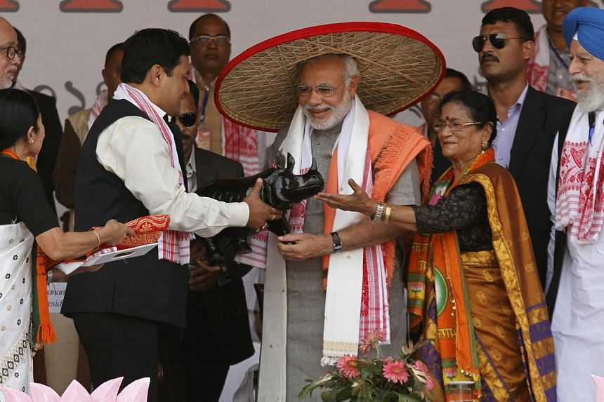 """Gujarat's chief minister and Hindu nationalist Narendra Modi (C), the prime ministerial candidate for India's main opposition Bharatiya Janata Party, wearing a """"Japi"""" (a traditional hat of Assam) receives a wooden Rhino by his supporters during a ral"""