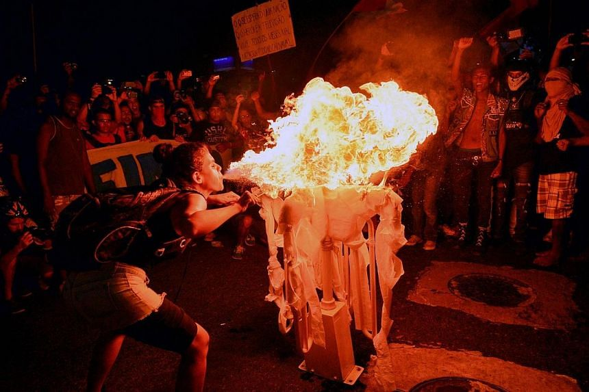 A woman blows fire to a bus fare gate removed during a joint protest against a rise on public bus fares and the Brazil 2014 FIFA World Cup, in Rio de Janeiro, Brazil, on February 10, 2014. -- PHOTO: AFP