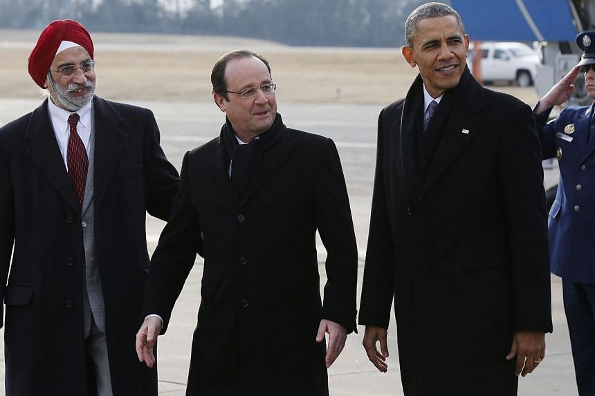 United States President Barack Obama (right) and French President Francois Hollande (centre) are greeted by Charlottesville Mayor Satyendra Huja (Left) upon arrival at Charlottesville Albemarle Airport on Feb 10, 2014. -- PHOTO:REUTERS