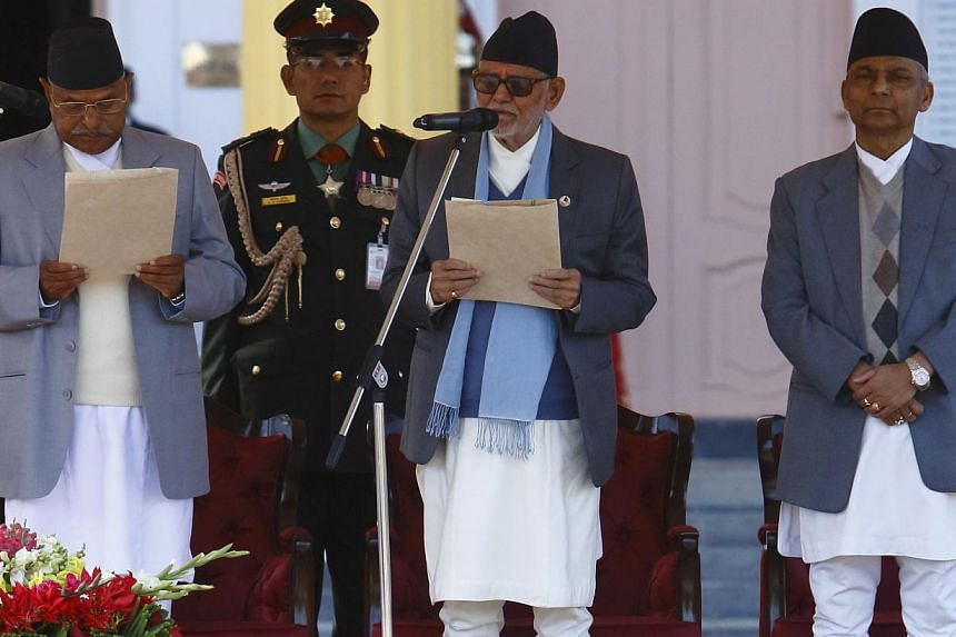 "Nepal's President Ram Baran Yadav (left) administers the oath of office to the newly-elected Nepalese Prime Minister Sushil Koirala (centre) in the presence of Chairman of the Interim Election Council Khil Raj Regmi at the presidential building ""Shit"