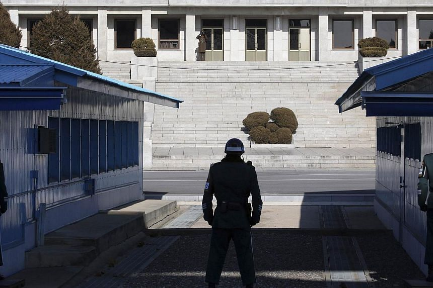 A North Korean soldier (top left) keeps watch as South Korean soldiers stand guard at the truce village of Panmunjom in the demilitarised zone separating the two Koreas, north of Seoul, on Feb 6, 2014.North and South Korea will hold rare high-l
