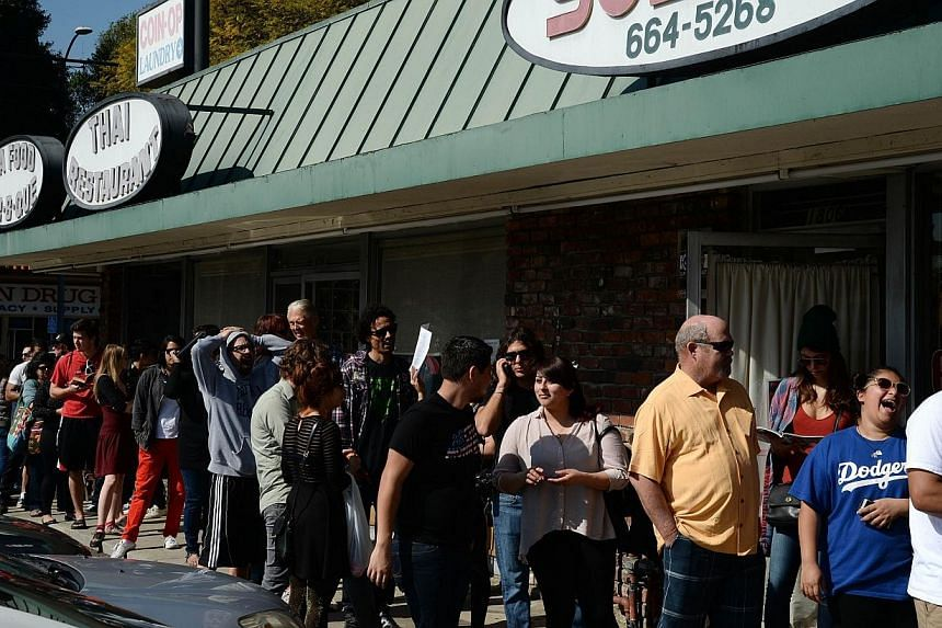 """People wait in a long line to get into a coffee shop named """"Dumb Starbucks"""", on Feb 10, 2014, in the Los Feliz area of Los Angeles. -- PHOTO: AFP"""