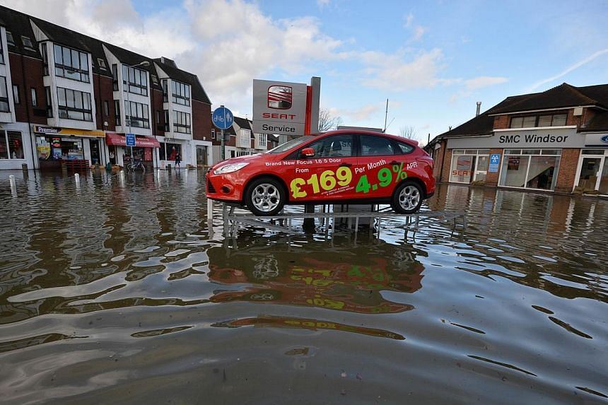 A display car at a car dealership has been left on a ramp above floodwater in Datchet in Berkshire, South East England, on Feb 10, 2014.The floodwaters are rising in Datchet but there appears to be no one around to help except David Cannon the