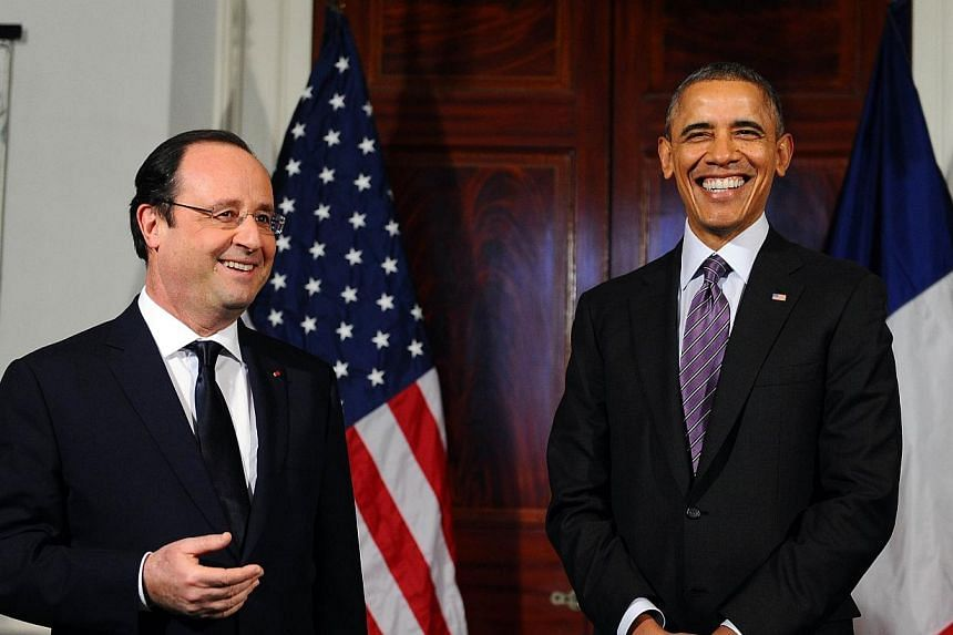 US President Barack Obama (right) laughs as his French counterpart Francois Hollande makes a statement to the media followoing their tour of the Third US President Thomas Jefferson, one of the US earliest envoys to France, residence -Monticello- whic