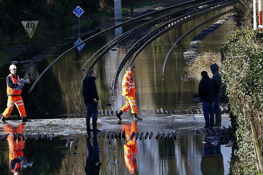 Railway workers are seen crossing the tracks after the river Thames flooded the railway in the village of Datchet, southern England on Feb 10, 2014. Residents of a village west of London evoked the wartime spirit that got the British capital through