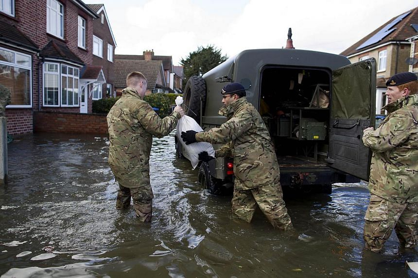 British army soldiers distribute sandbags to residents of houses surrounded by floodwaters in Egham on Feb 11, 2014. -- PHOTO: AFP