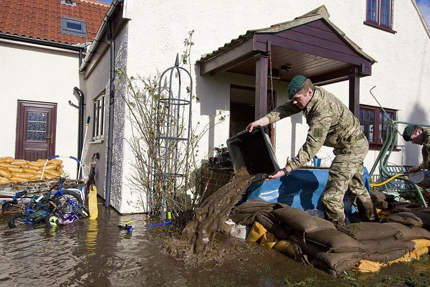 British Royal Marines help lay sandbags and remove water from around a home threatened by floodwaters during flood relief operations in Moorland, some 19km north-east of Taunton on Feb 7, 2014. -- FILE PHOTO: AFP