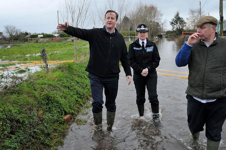 British Prime Minister David Cameron (left) with Bridgwater and West Somerset MP, Ian Liddell-Grainger (right) during a visit to Goodings Farm in Fordgate, Somerset on Feb 7, 2014. -- FILE PHOTO: AFP