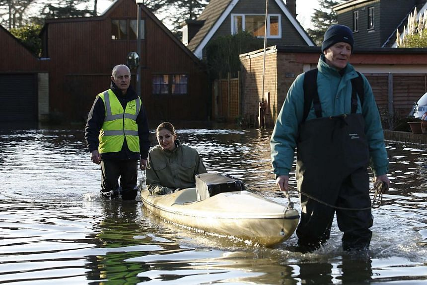 A woman is floated by canoe through flood water after the river Thames flooded the village of Wraysbury, southern England, on Feb 11, 2014. -- PHOTO: REUTERS