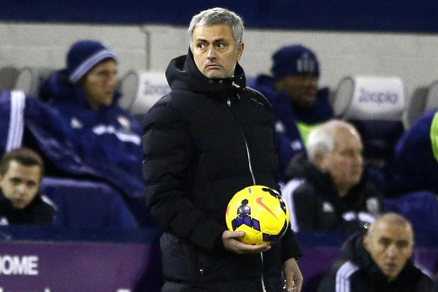 Chelsea manager Jose Mourinho holds the ball during the team's English Premier League soccer match against West Bromwich Albion at the Hawthorns in West Bromwich, central England, on Feb 11, 2014.Chelsea's title challenge suffered a setback whe