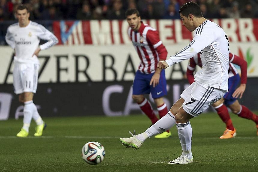 Real Madrid's Cristiano Ronaldo scores the team's second goal from the penalty spot against Atletico Madrid during their Spanish King's Cup semi-final second leg soccer match at Vicente Calderon stadium in Madrid, Feb 11, 2014. -- PHOTO: REUTERS