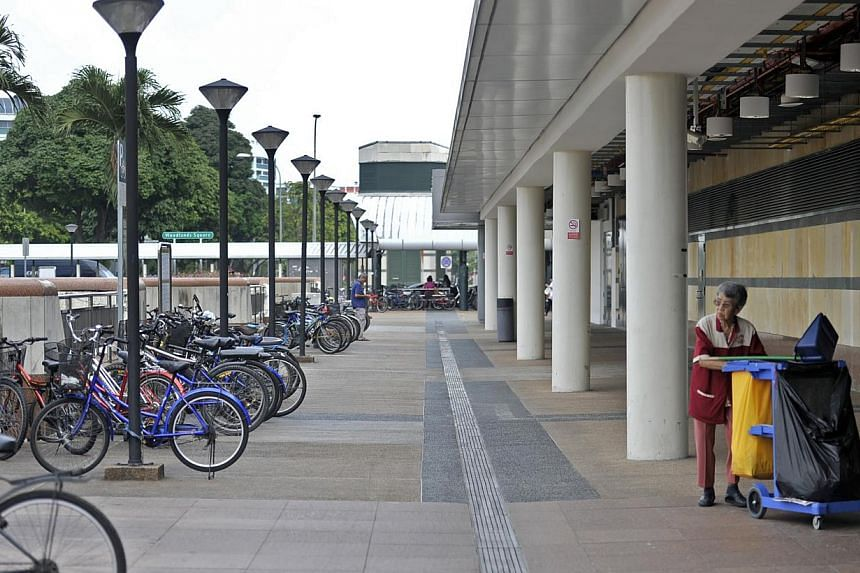 A cleaning lady makes her rounds at Woodlands MRT station on Feb 4, 2014. -- ST FILE PHOTO: MATTHIAS HO