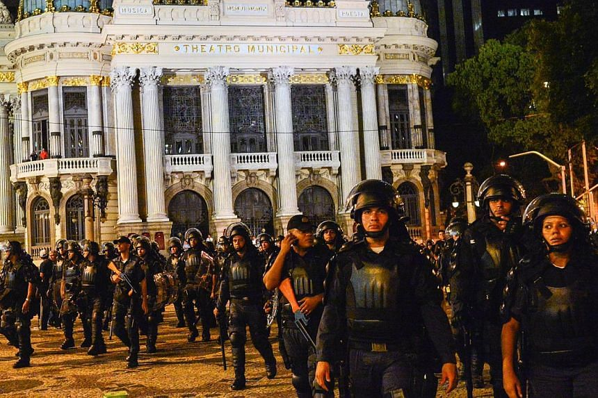 Riot policemen follow demonstrators during a joint protest against a rise on public bus fares and the Brazil 2014 FIFA World Cup, in Rio de Janeiro, Brazil, on Feb 10, 2014. A Brazilian journalist has died of a head injury sustained in a Rio street p