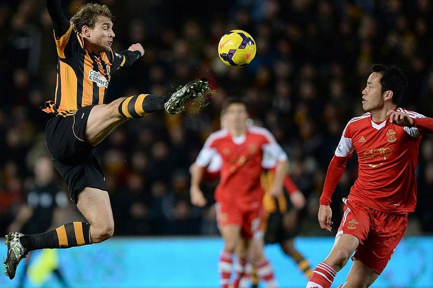 Southampton's Maya Yoshida (Left) is challenged by Hull City's Nikica Jelavic during their English Premier League soccer match at the KC Stadium in Hull, northern England on Feb 11, 2014. Southampton extended their unbeaten run to six matches on Tues