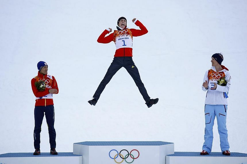 Winner Germany's Eric Frenzel (centre) jumps on the podium as second-placed Japan's Akito Watabe (left) and third-placed Norway's Magnus Krog (right), applaud, during the flower ceremony for the Nordic Combined individual normal hill 10km event of th